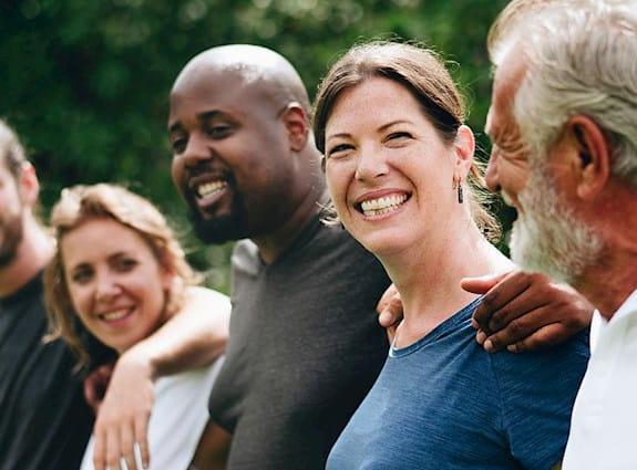 Groupe de six personnes les bras posés sur les épaules les uns des autres.