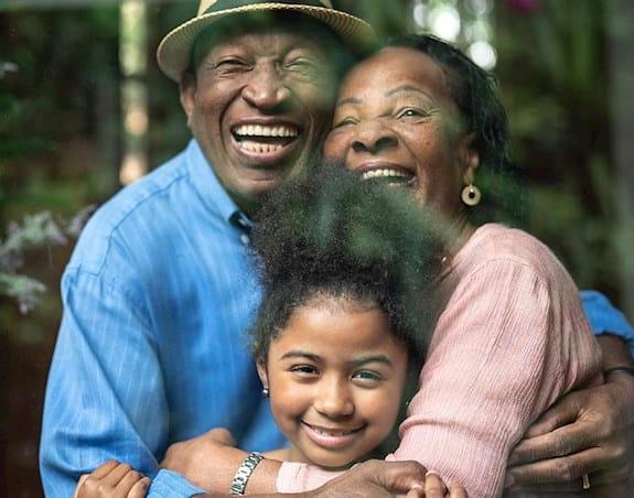 Deux parents enlaçant leur fille en souriant à la caméra.