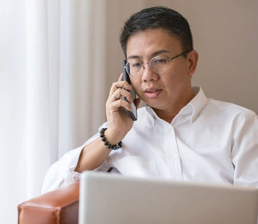 A man talks on his cell phone near his laptop