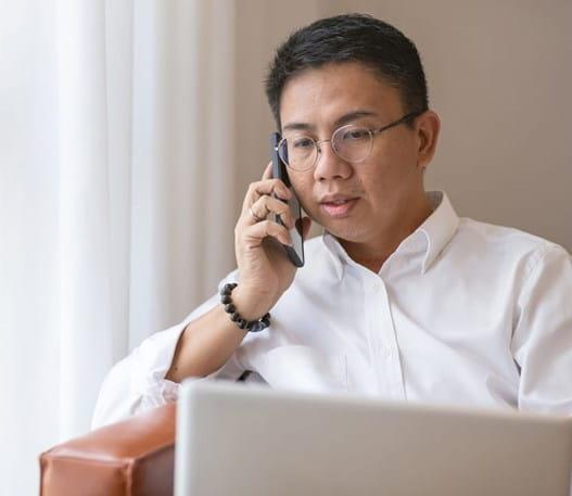 Homme regardant l'écran de son ordinateur portable en parlant au téléphone cellulaire.