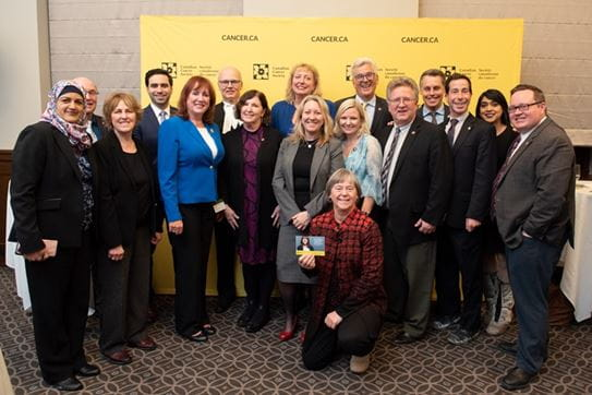CCS staff and government officials pose together in front of a large yellow CCS banner