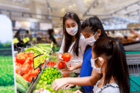 Une mère et ses deux enfants portent des masques protecteurs lorsqu'ils magasinent des fruits et légumes dans une épicerie