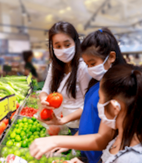 A mother and her two children wear protective face masks while shopping for fruit and vegetables in a grocery store