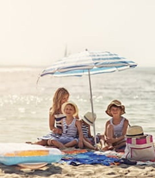 Family sitting on a beach under a sun umbrella