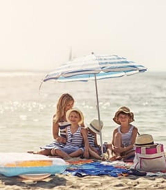 Une famille assise sur la plage, sous un parasol
