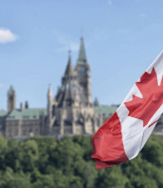Le drapeau canadien flottant et, à l'arrière-plan, la Colline du Parlement