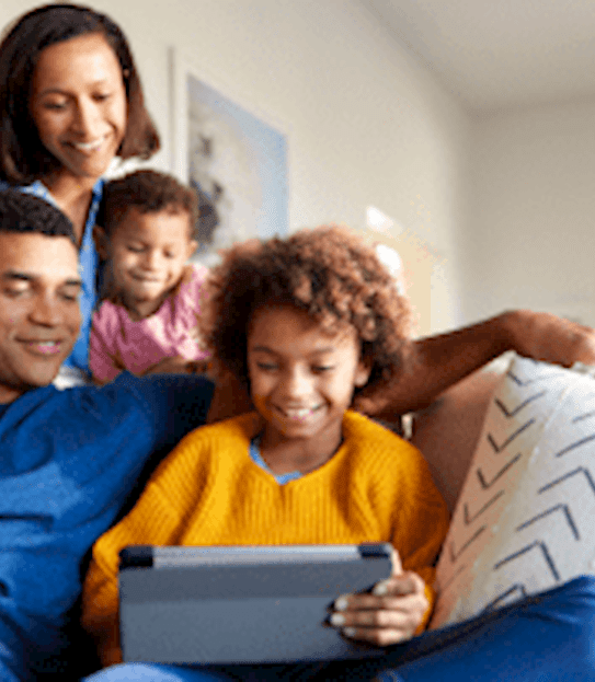 A family sitting together and looking at a laptop