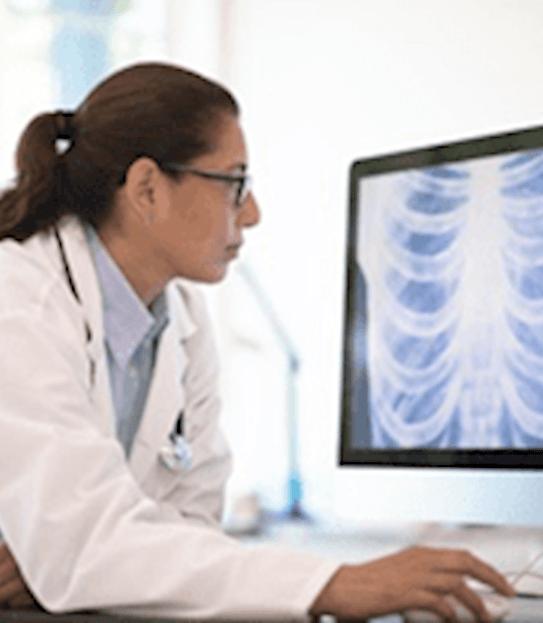 Une femme médecin assise à son bureau regardant le radiogramme d'un thorax sur son ordinateur.