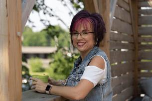 Bonnie, survivante de cancer du sein, qui sourit, avec une tasse à la main