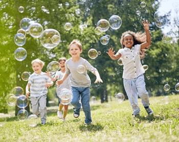 De jeunes enfants souriants poursuivant des bulles de savon lors d'une journée chaude et ensoleillée