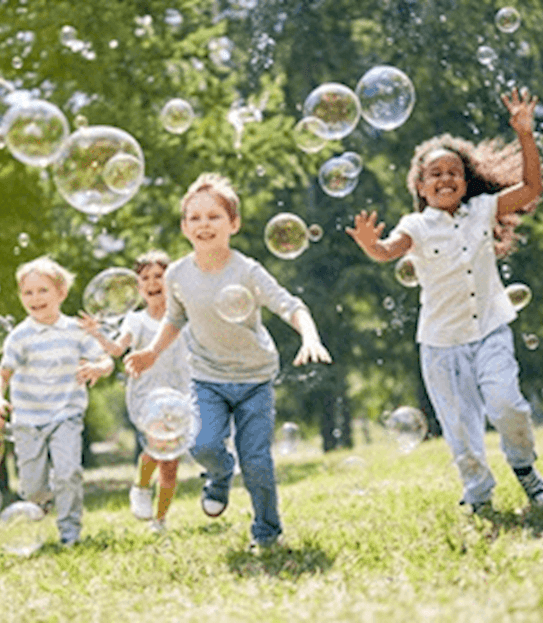 Young children smiling and enjoying a warm, sunny day by chasing soap bubbles