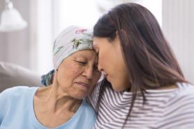 Une femme âgée atteinte d'un cancer et portant un couvre-chef, dans une étreinte avec sa fille adulte
