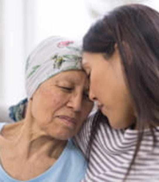 An elderly woman with cancer and wearing a head covering is embracing her adult daughter. They are sitting on a couch and their foreheads are touching.