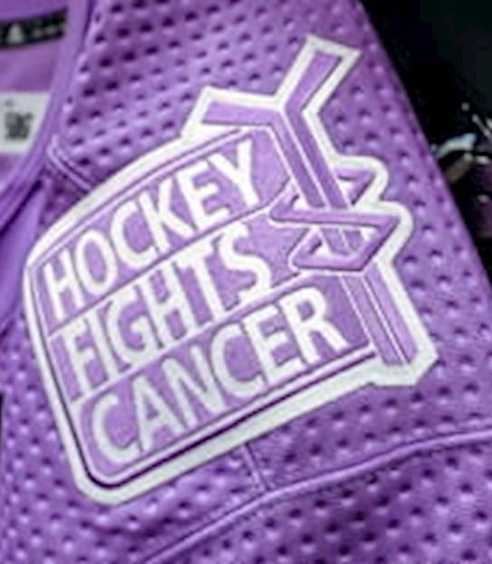 A hockey jersey with a hockey fights cancer patch.