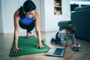 Une mère faisant ses exercices pendant que son enfant joue sur le sol, près d'elle