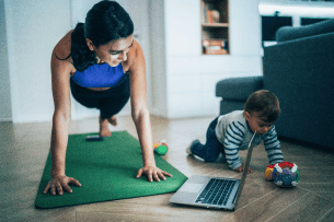 A mom exercises while her child plays on the floor next to her.