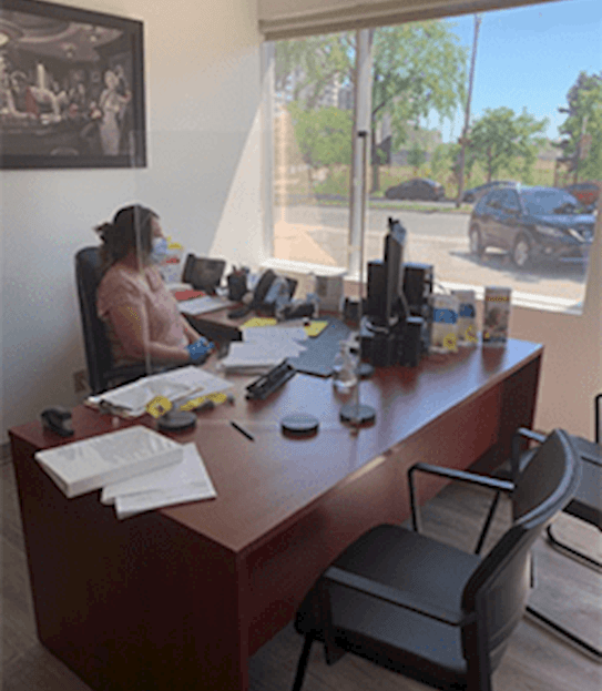 Une femme portant un masque, assise à son bureau, derrière un écran protecteur en verre acrylique