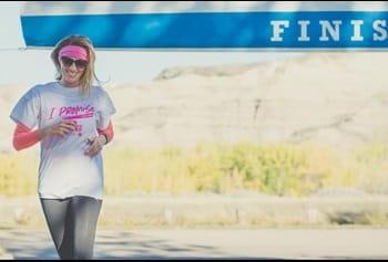 Une femme franchit la ligne d'arrivée à la Course à la vie CIBC de la Société canadienne du cancer.