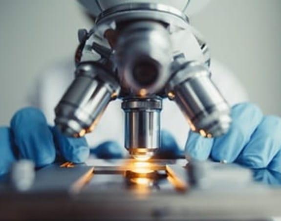 A researcher using a microscope.