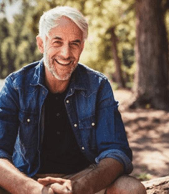 Un homme d'âge moyen assis près d'un lac, regardant la caméra et souriant.