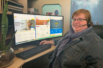 Carrie Van Lingen, Cancer Information Specialist, sitting at a computer.