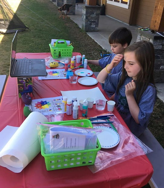 Two children sit at a park bench covered with an assortment of craft supplies