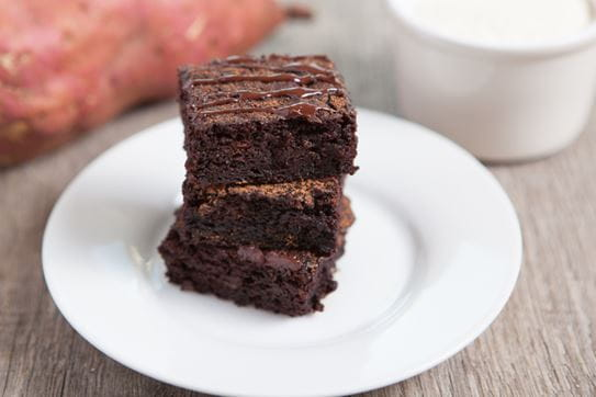A close up of three chocolate sweet potato bars stacked on a plate
