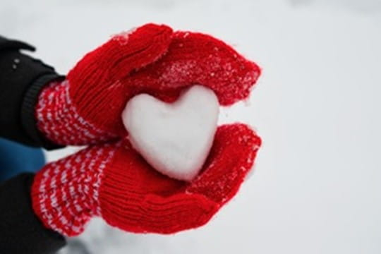 Hands in red mittens holding heart made out of snow