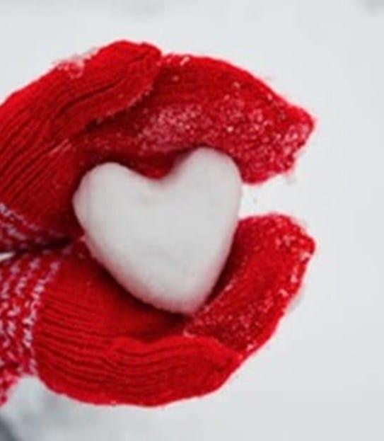 Mains dans des mitaines rouges tenant un cœur fait de neige.