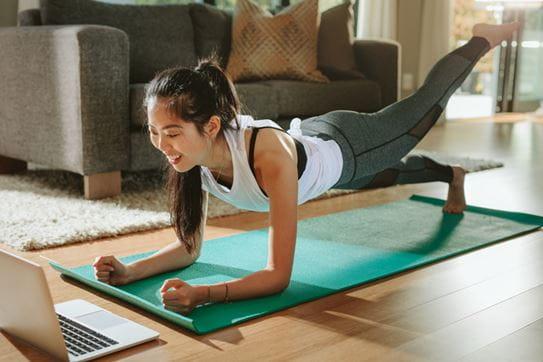 Femme faisant du yoga en regardant son écran d'ordinateur.