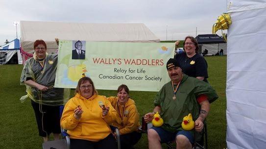 Cinq personnes tenant des canards de plastique, assis autour d'une affiche où on peut lire « Wally's Waddlers » Relais pour la vie, Société canadienne du cancer.