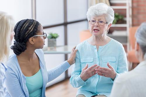 Une femme montrant de la compassion en touchant l'épaule d'une femme plus âgée qui parle lors d'une rencontre en groupe