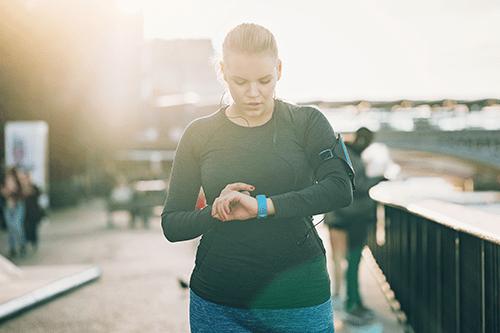 Une femme en tenue de sport faisant de la course pied à l'extérieur regarde sa montre intelligente.