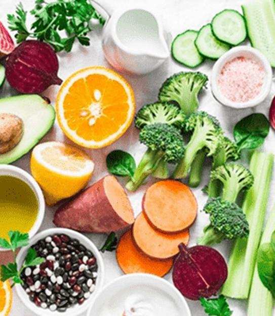 Un comptoir de cuisine rempli de légumes, de fruits et de grains entiers, vu de haut.
