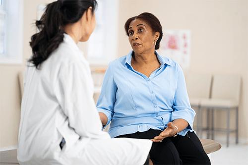 Une femme dans la cinquantaine discute avec son médecin.