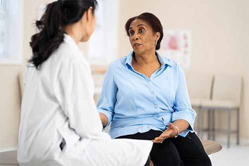An older woman sitting and speaking to her doctor