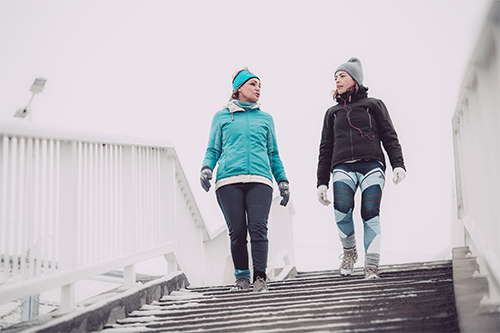 Two women walking down stairs lightly covered in snow