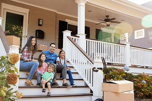 Les membres d'une famille sont assis à l'extérieur, dans l'escalier menant à leur maison.
