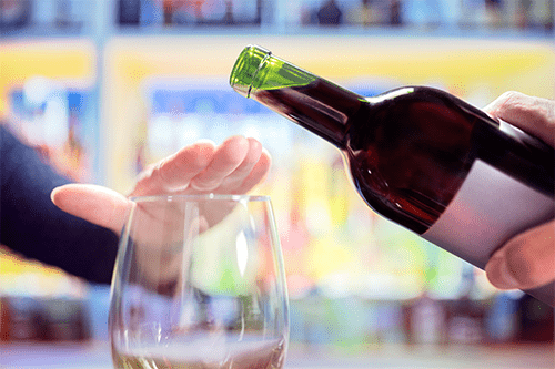 A hand showing a gesture of saying no to an offering of wine