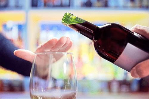 Une personne recouvre de la main le dessus d'une coupe vide pour empêcher qu'on y verse du vin.