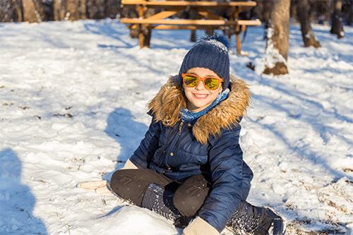 Un garçon portant des lunettes de soleil joue dans la neige.