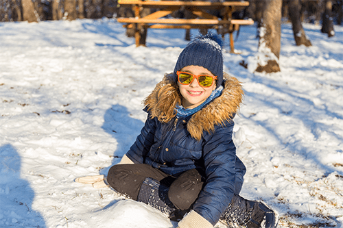 A kid wearing sunglasses and sitting in the snow