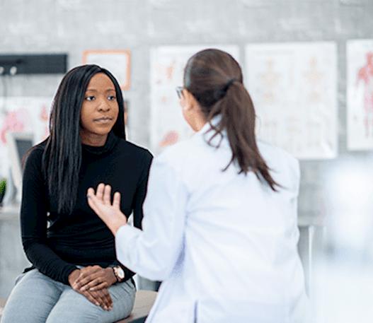 Une jeune femme discute avec son médecin.