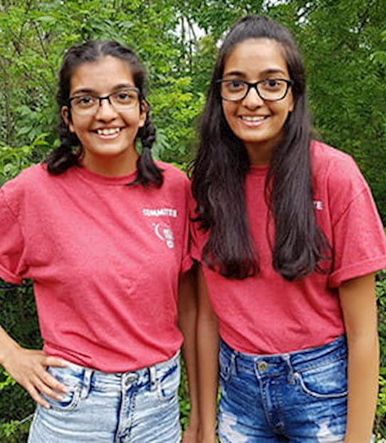 Anika and Eesha standing together and smiling