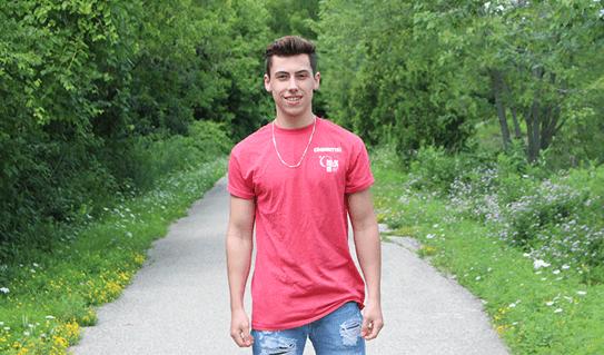 Jacob souriant et portant une chemise de bénévole CCS