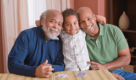 A young boy smiling and sitting between his father and his grandfather