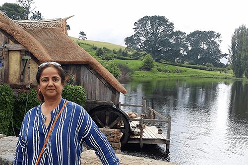 Anjum standing infront of a house by a lake