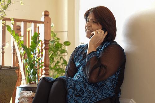 Sharon s'asseyant sur ses escaliers parlant sur son téléphone