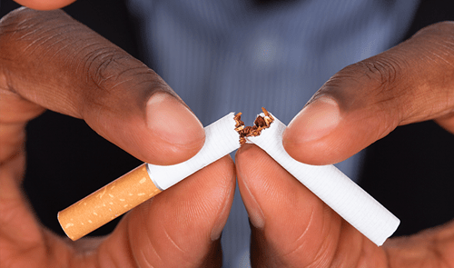 A close up of a cigarette being broken