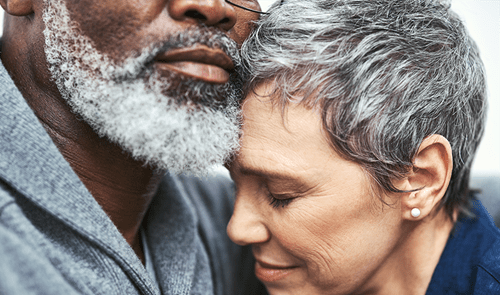 A close up of a man and woman hugging